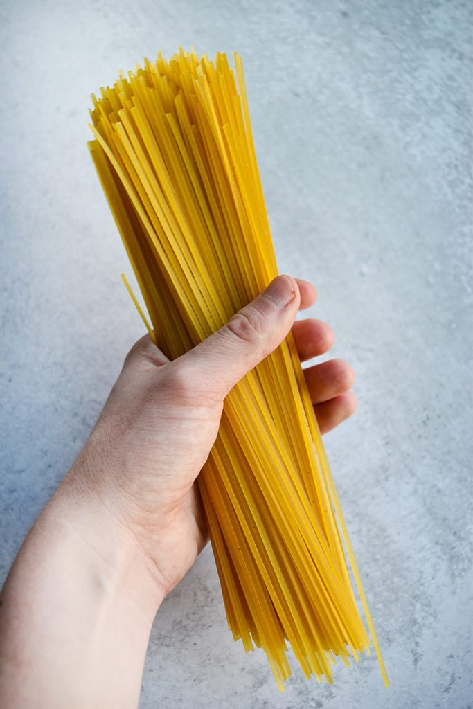 a hand holding pasta