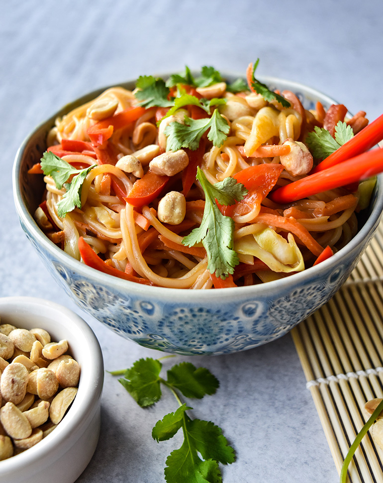 Asian noodles in a blue bowl with chopsticks