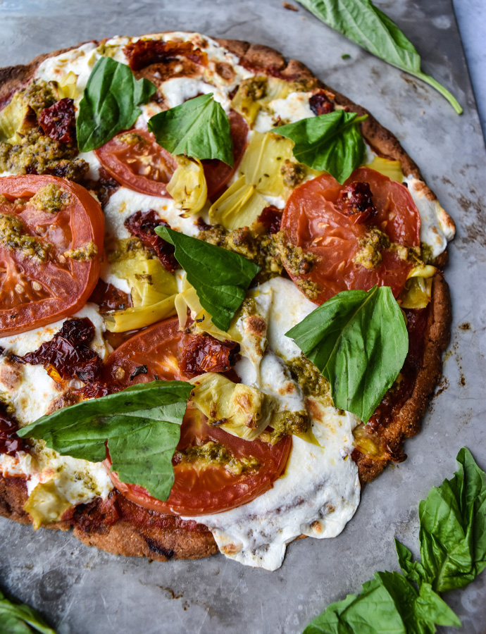 Cheesy Mozzarella, Tomato, Artichoke, and Pesto Pizza